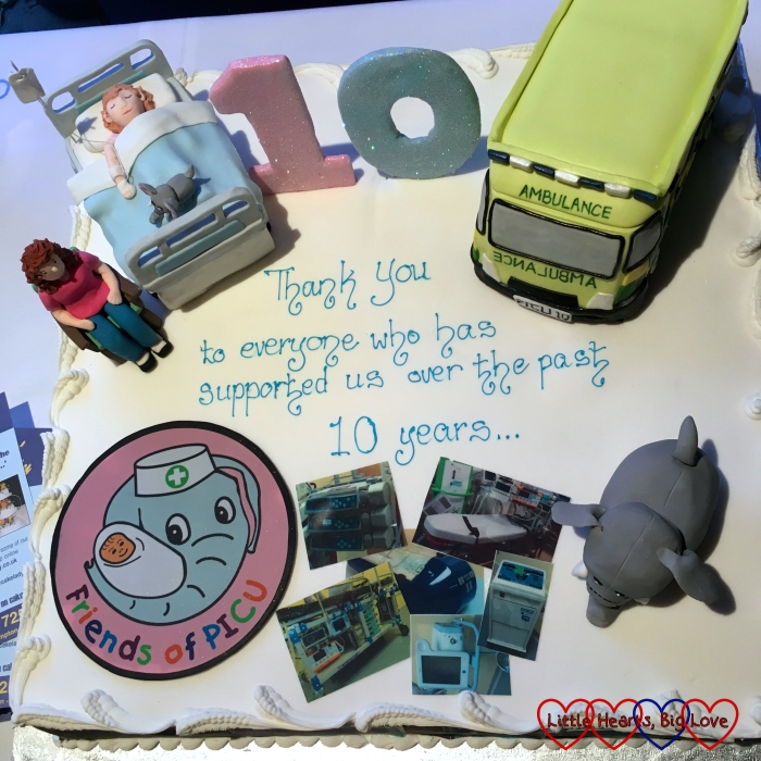 The 10th anniversary cake for Friends of PICU showing the elephant logo, an elephant, an ambulance and a parent sitting by their child in a hospital bed