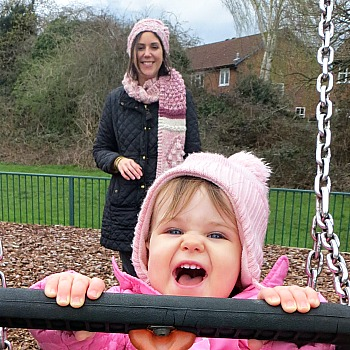 Susie from This Is Me Now wearing hat and scarf and pushing her daughter in a toddler swing