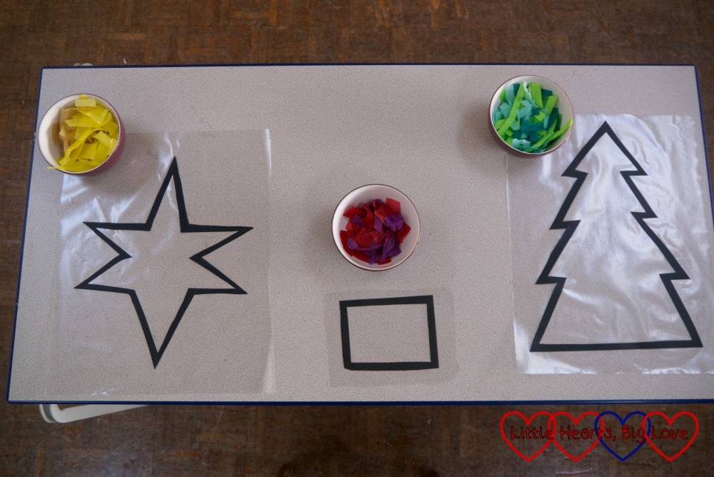 The outlines of the tree, pot and star laid out on sticky-back plastic with bowls of tissue paper ready to be used