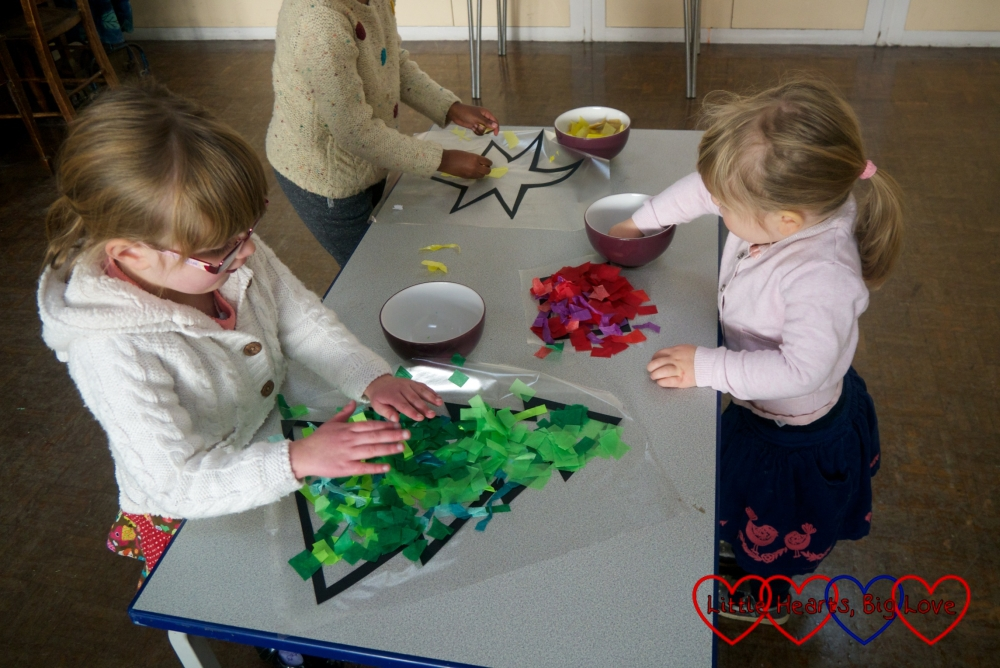 Jessica, Sophie and a friend sticking tissue paper on to the cut out shapes of a tree, pot and star