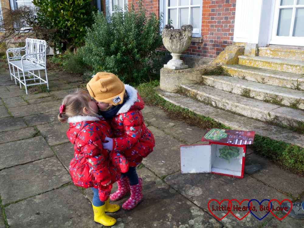 Jessica and Sophie sharing a kiss next to an advent box containing mistletoe
