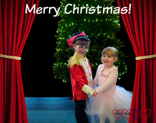 "Jessica dressed in a soldier costume and Sophie in a pink tutu standing in front of a Christmas tree with stage curtains either side of them and the text ""Merry Christmas"""