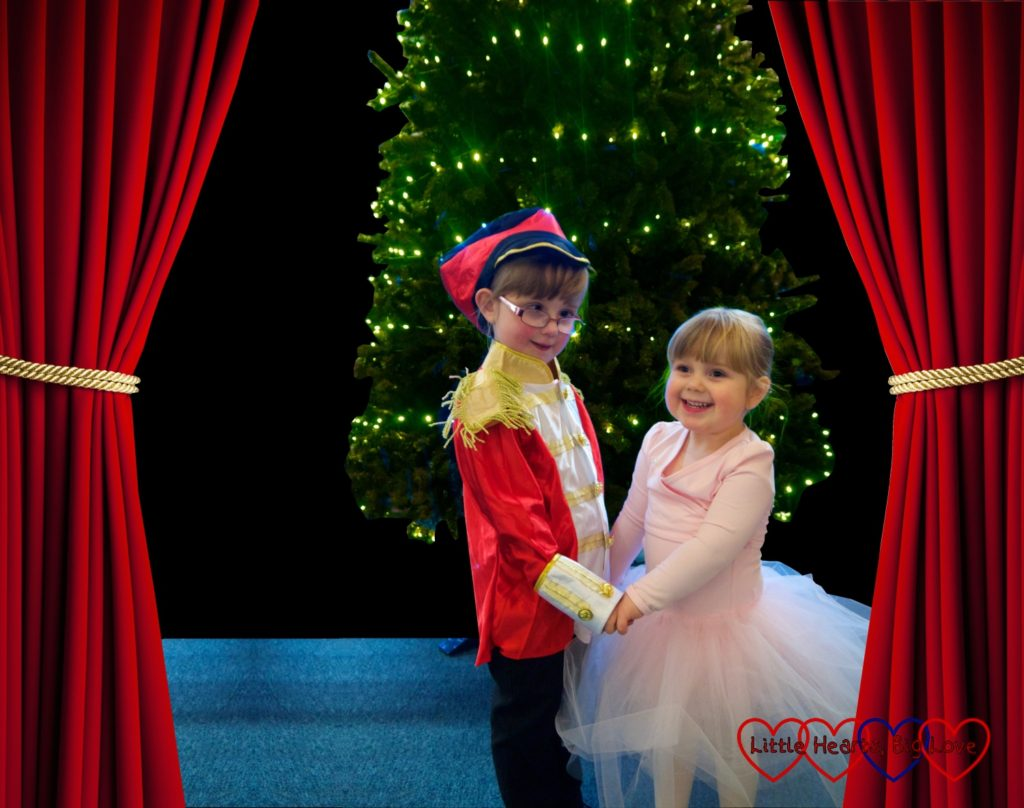 Jessica dressed in a soldier costume and Sophie in a pink tutu standing in front of a Christmas tree with stage curtains either side of them