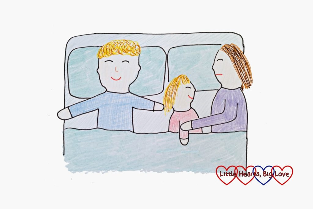 A drawing of a mummy, daddy and child sleeping in a double bed