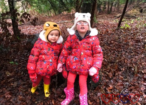 Jessica and Sophie sitting together on a log in the woods