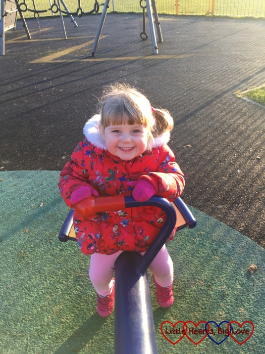 Sophie giving me a big smile while sitting on the seesaw
