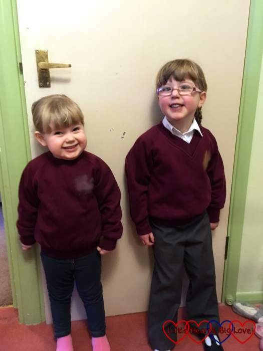 Sophie in her preschool jumper standing next to Jessica in her school uniform
