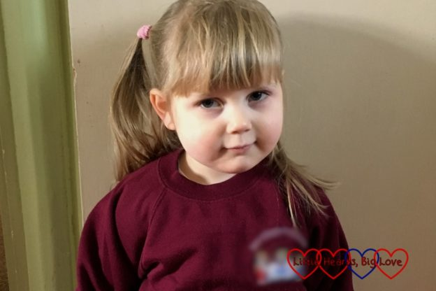 Sophie wearing her preschool jumper, ready for her first day