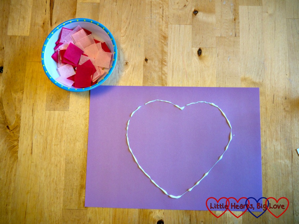 A heart shape made with glue on a sheet of cardboard and a bowl containing pieces of cut up tissue paper