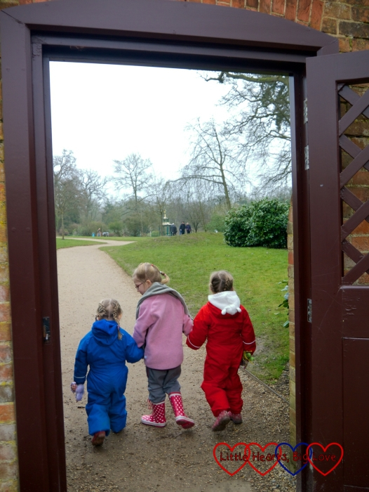 Jessica and Sophie holding hands with their friend P and heading off through a gate at Cliveden