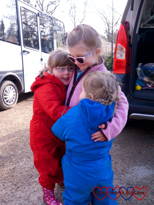 Jessica and Sophie giving their friend P a big hug