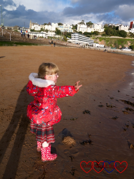 Jessica holding out her hand to stop the tide from coming in