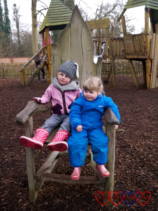 Sophie and P sitting on a big wooden chair in the play area at Cliveden