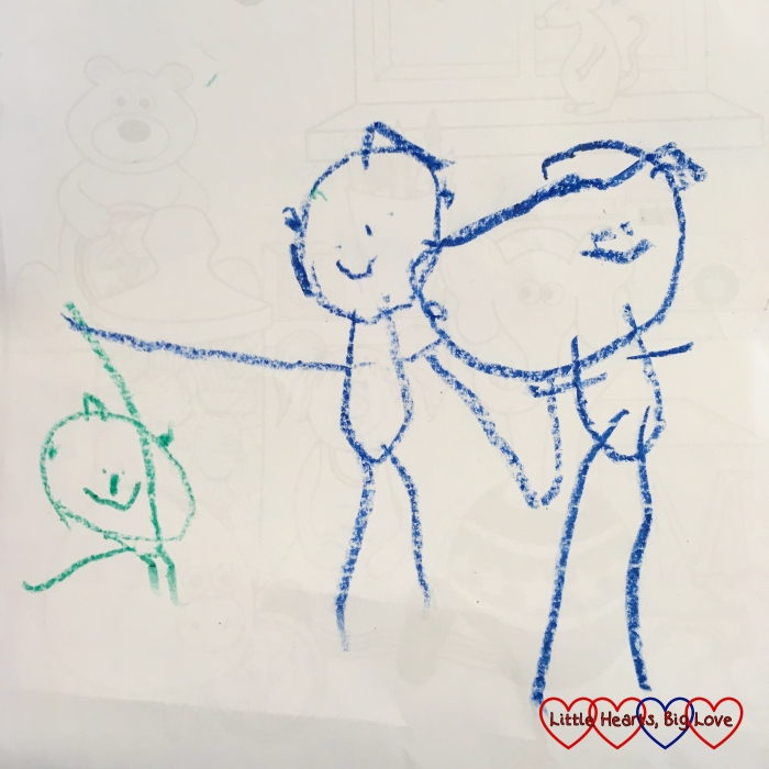 Sophie's drawing of herself in green, holding hands with Jessica who is standing next to Mummy