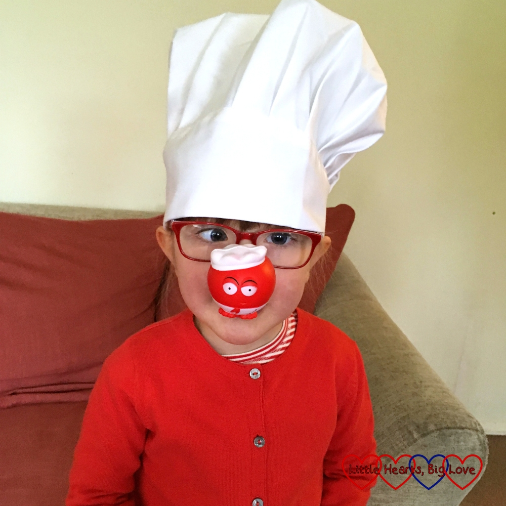Jessica wearing a red cardigan, white chef's hat and a chef-character red nose for Red Nose Day