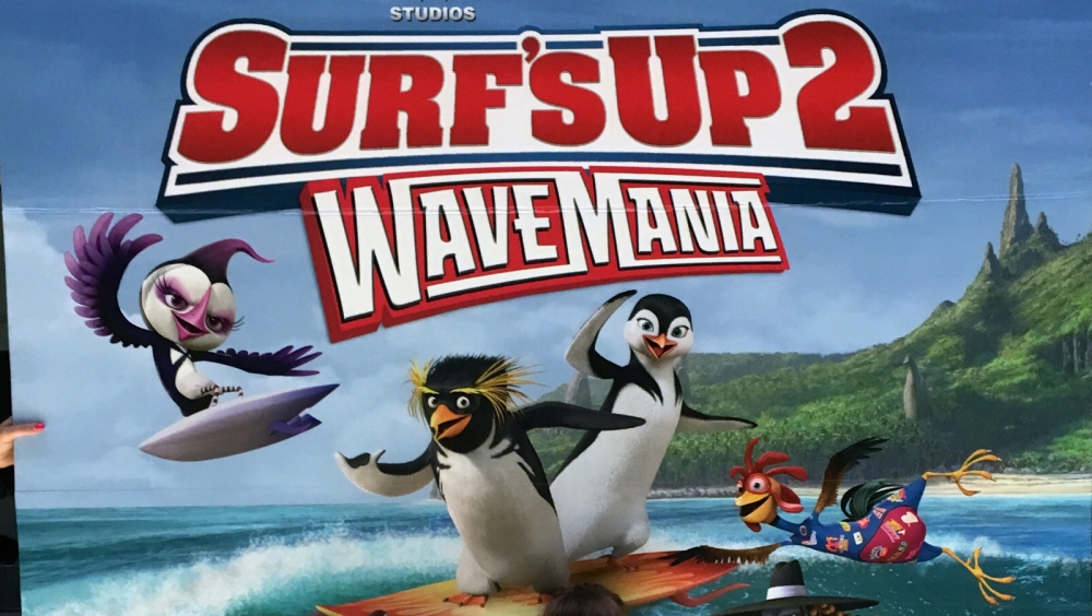 Part of the Surf's Up 2: Wavemania poster showing the title and some of the surfing penguins