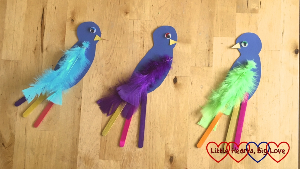Three parrots made from blue cardboard, with coloured feathers (blue, purple and green) and tail feathers made of different coloured craft sticks