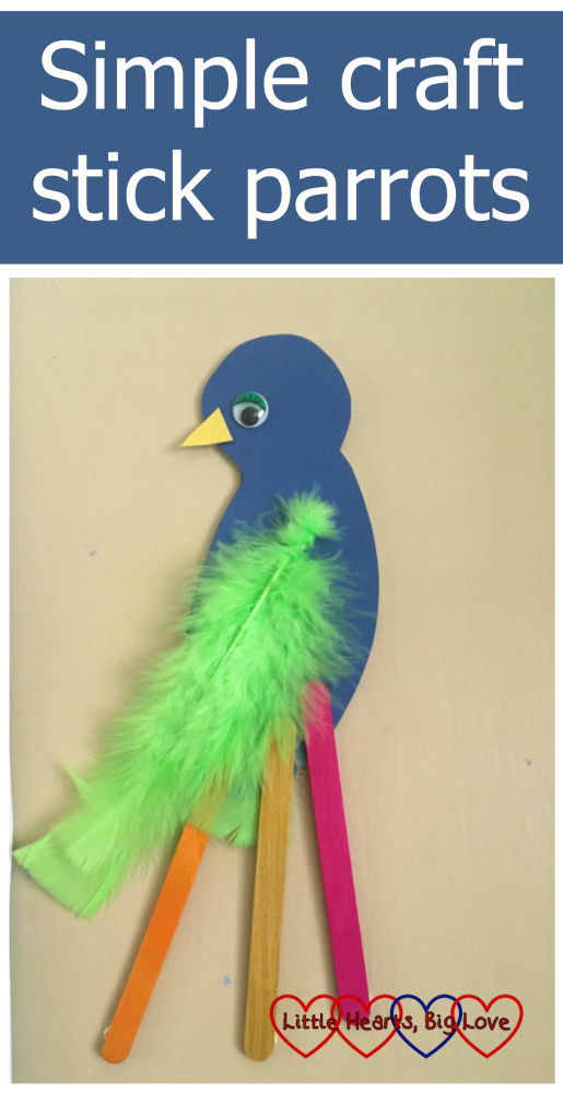 A blue coloured cardboard parrot with green feathers and pink, yellow and orange craft sticks to make the tail feathers