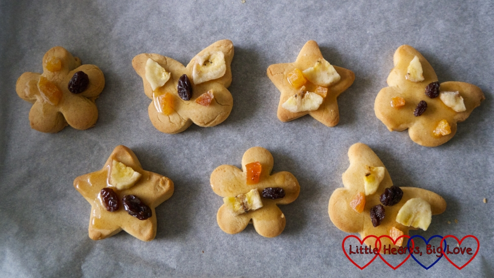 Seven shaped biscuits decorated with dried fruit on a baking sheet