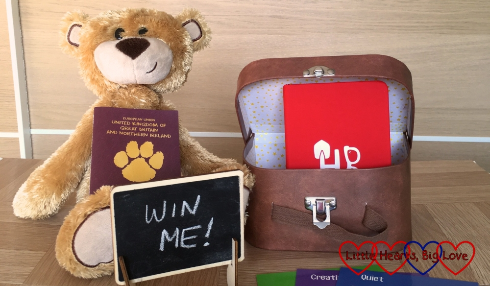 "A My Holibob Bear with suitcase, journal, Pawsport and a chalk board sign saying ""Win me!"""