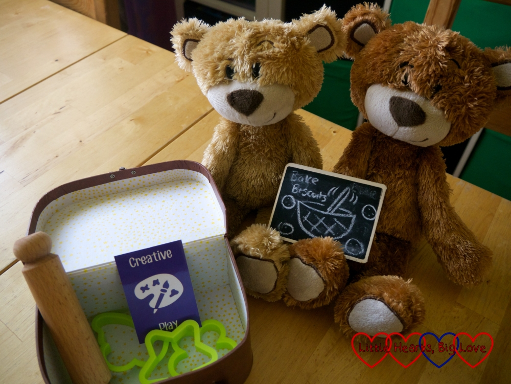 "The My Holibob Bears with a chalkboard saying ""bake biscuits"" and a suitcase containing the Creative Play card, a rolling pin and some cookie cutters"