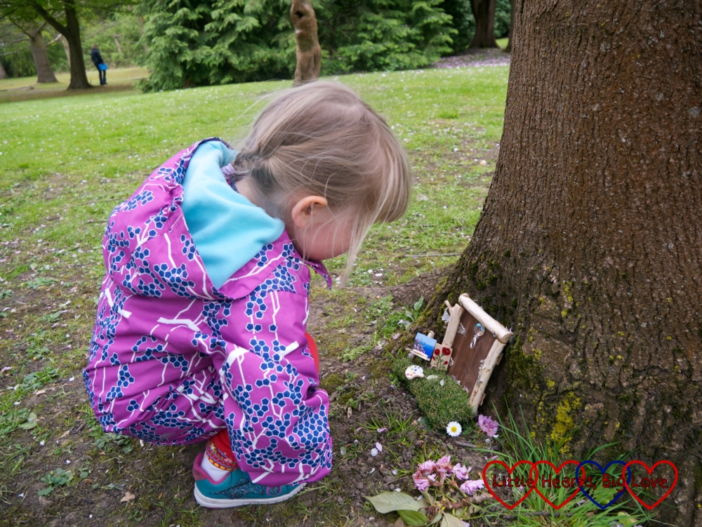 Sophie looking at a fairy door with miniature paintings outside