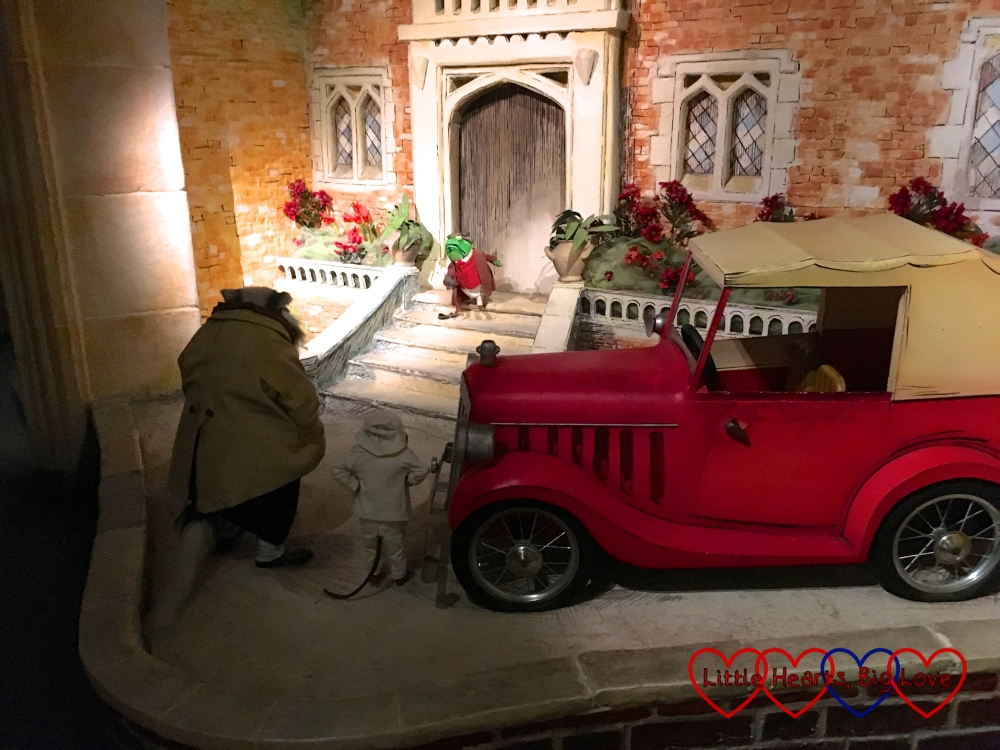 Toad on the steps of Toad Hall with his motor car outside