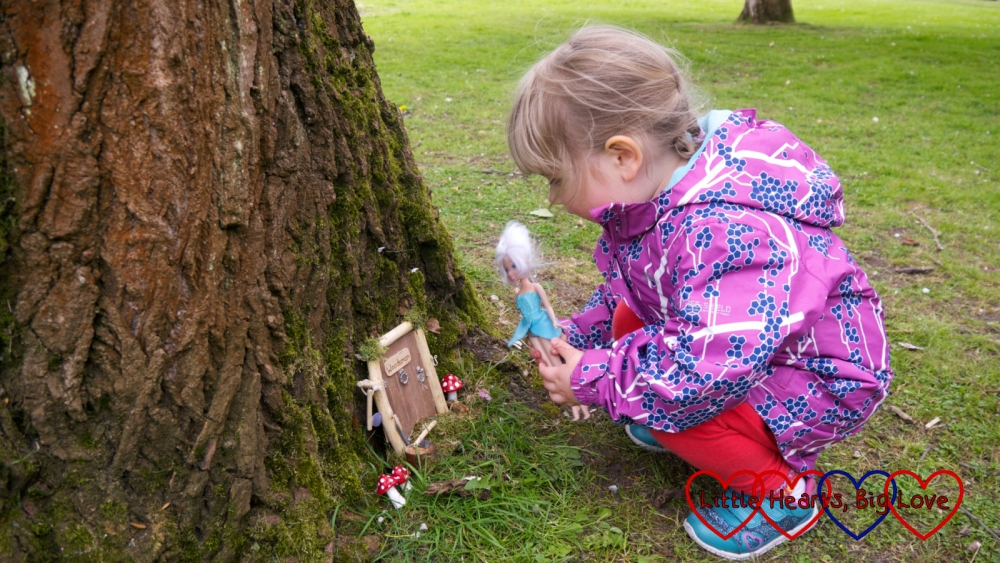 Sophie looking at one of the fairy doors with her Periwinkle fairy doll