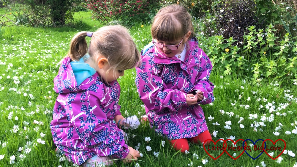 Jessica and Sophie picking up blossom petals in Grandma's garden