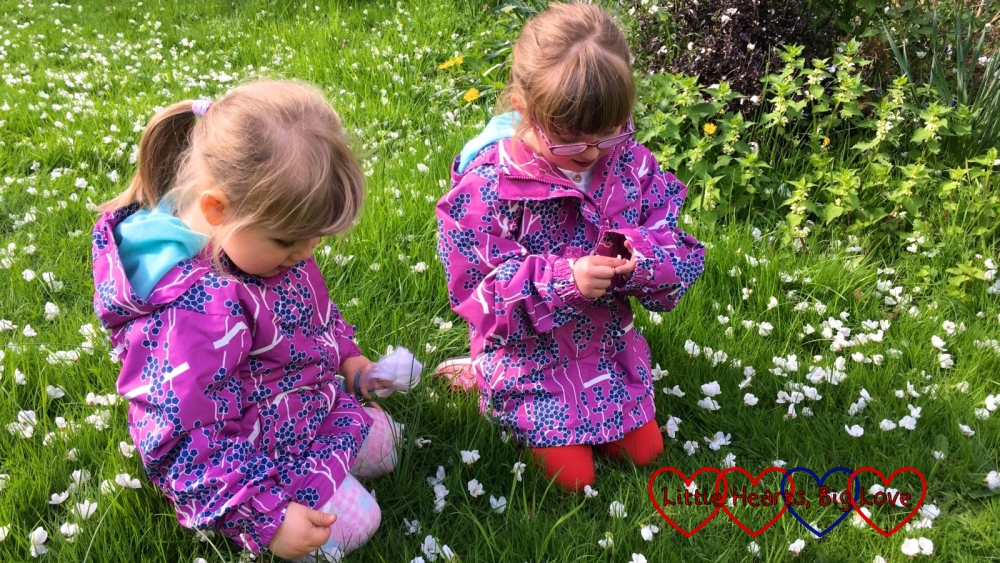 Jessica and Sophie sitting in Grandma's garden wearing their new Trespass jackets
