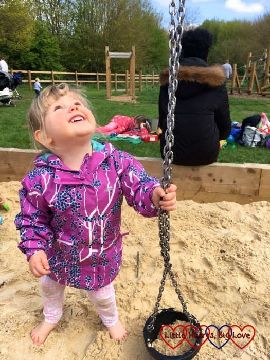Sophie wearing her Imogene waterproof jacket from Trespass while playing in a sandpit