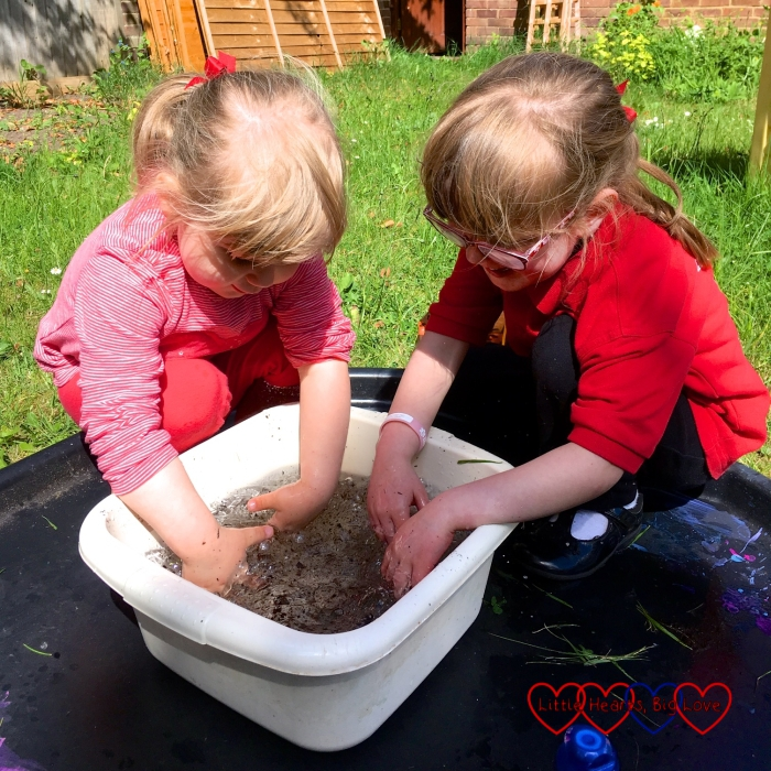 Jessica and Sophie mixing some soil into the water in the bowl