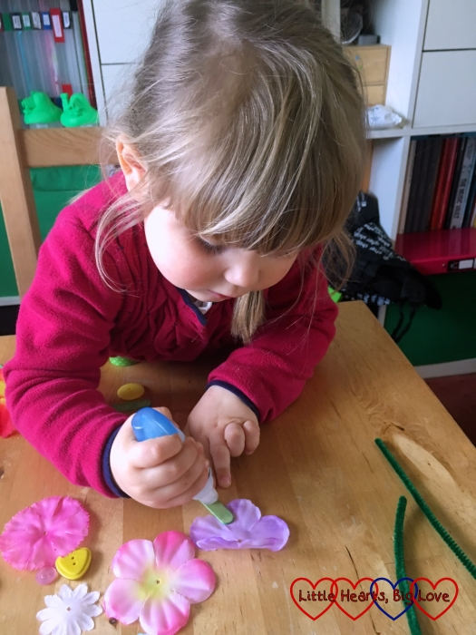 Sophie putting glue on a craft stick ready to add a flower shape