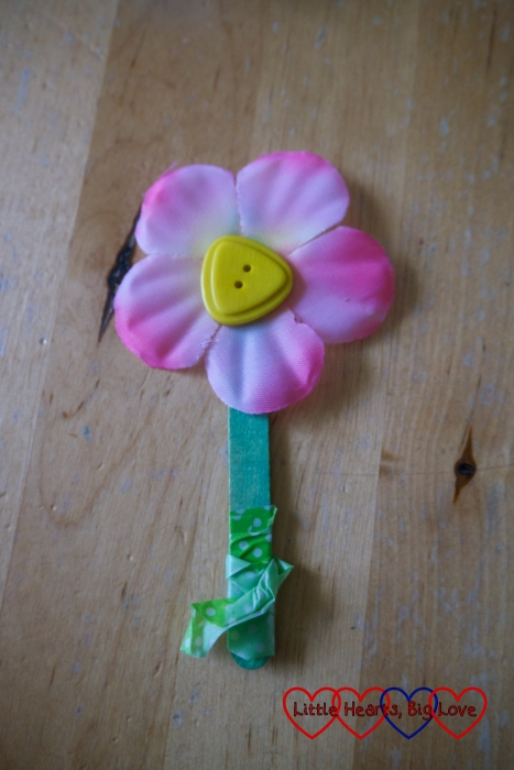A craft stick flower with a button in the middle of the flower