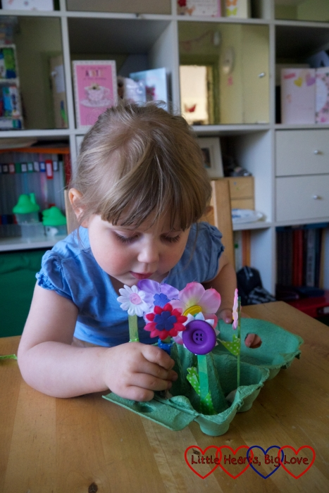 Sophie putting the flowers in the egg box using blu tack