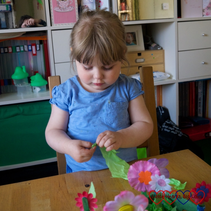Sophie tearing up green tissue paper for her egg box flower garden