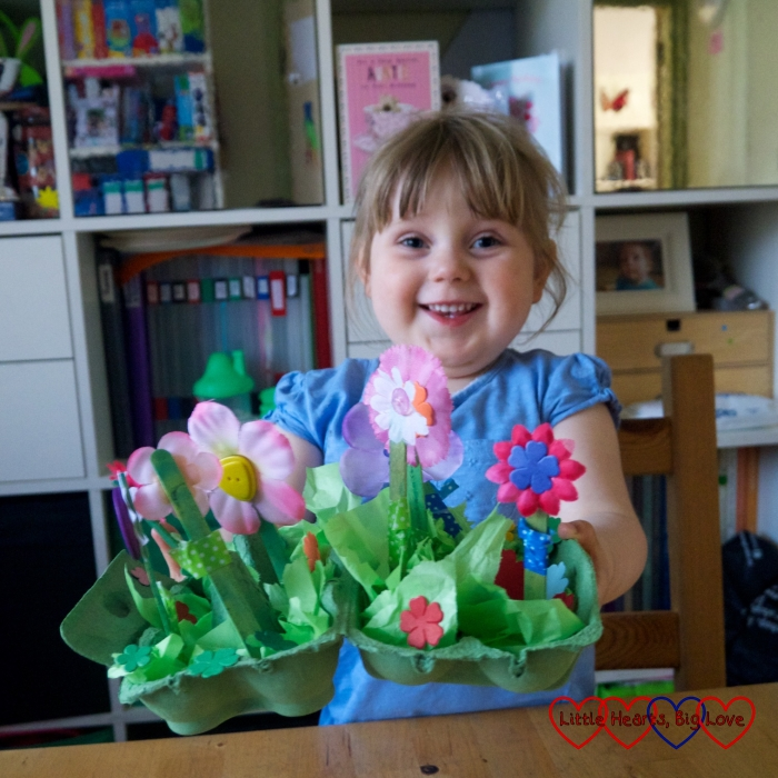 Sophie holding her egg box flower garden and grinning
