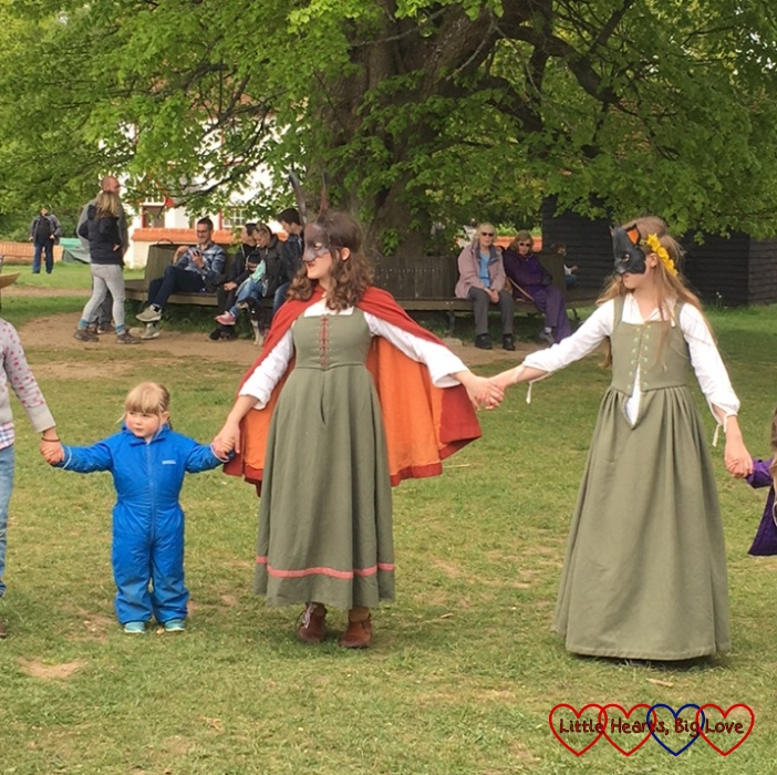 Sophie holding hands with two other dancers and joining in with the Elizabethan dancing