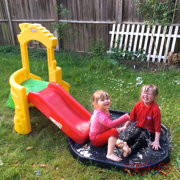 Jessica and Sophie sitting and splashing in the tuff spot with the slide next to it