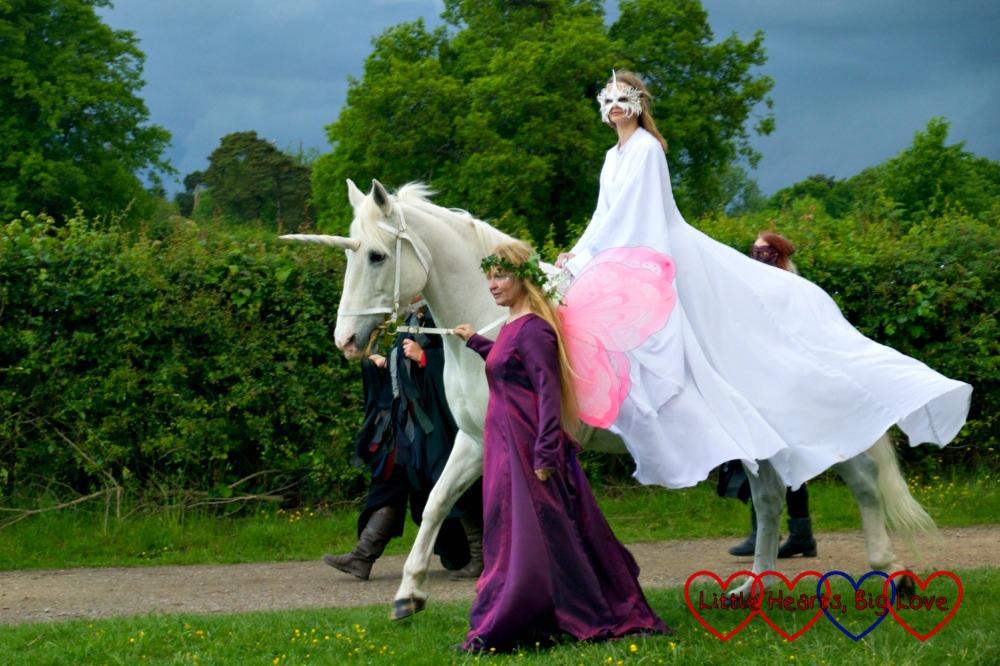 A fairy leading a unicorn with a princess riding on the back