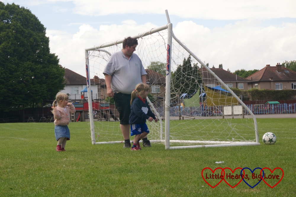Sophie and Jessica playing football with Daddy