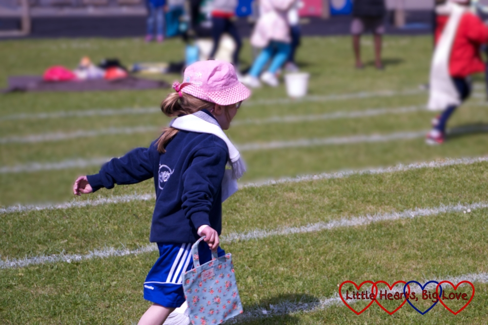 Jessica coming in last with her hat, scarf and bag in the obstacle race