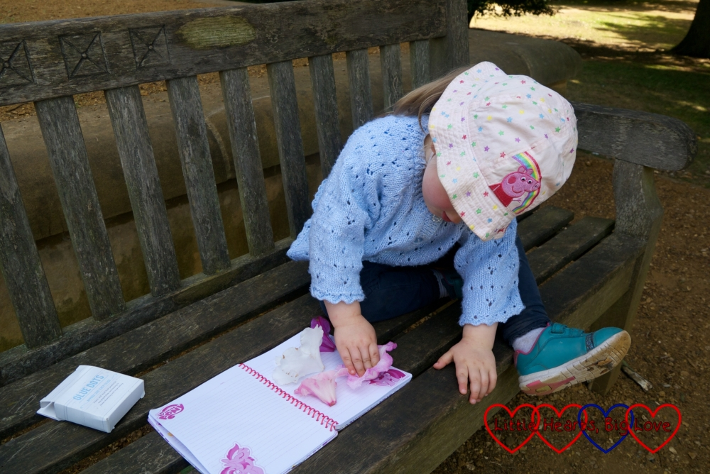Sophie sticking rhododendrons in her nature book