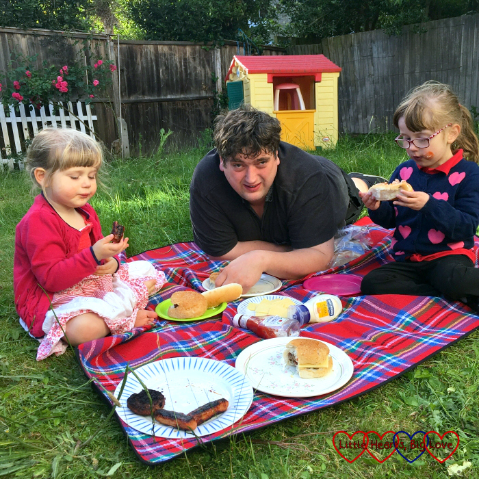 Sophie, hubby and Jessica sitting on the picnic blanket, enjoying a meal together