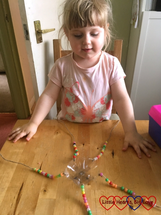 Sophie looking at the butterfly feeder with the beaded pieces of string splayed out on the table