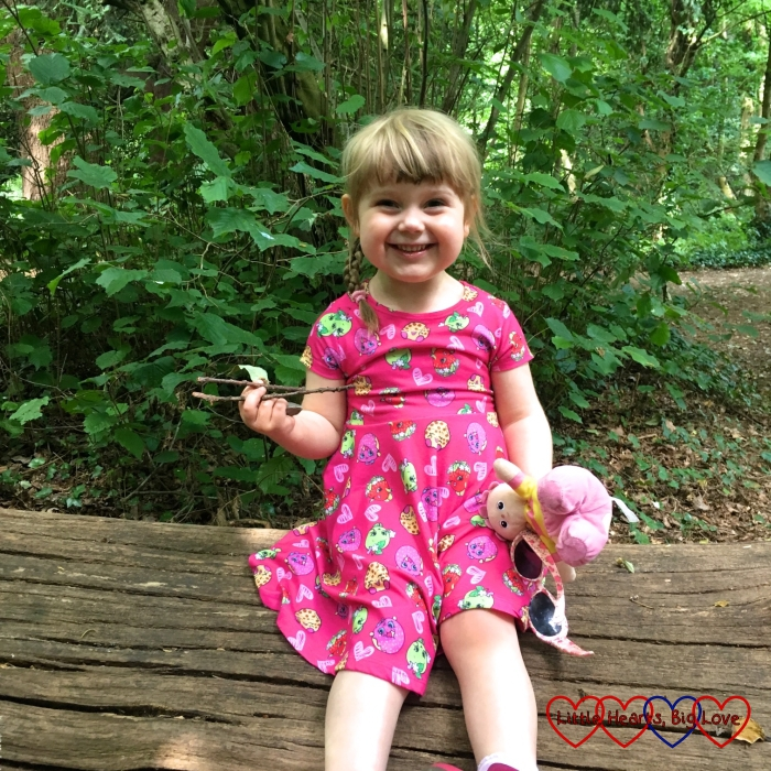 Sophie sitting on a log in the woods