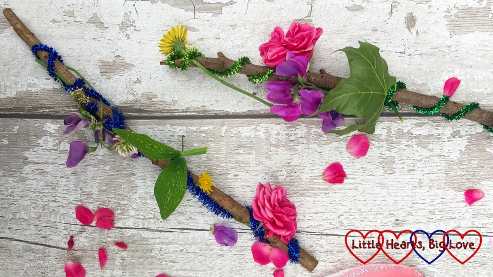 Two fairy wands made from sticks and decorated with glittery pipe-cleaners, roses, hawksbeard, sweetpea and leaves