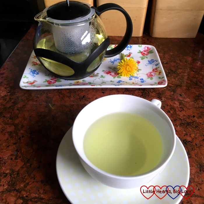 A pot of dandelion flower tea on tray with a dandelion flower and a cup of dandelion flower tea