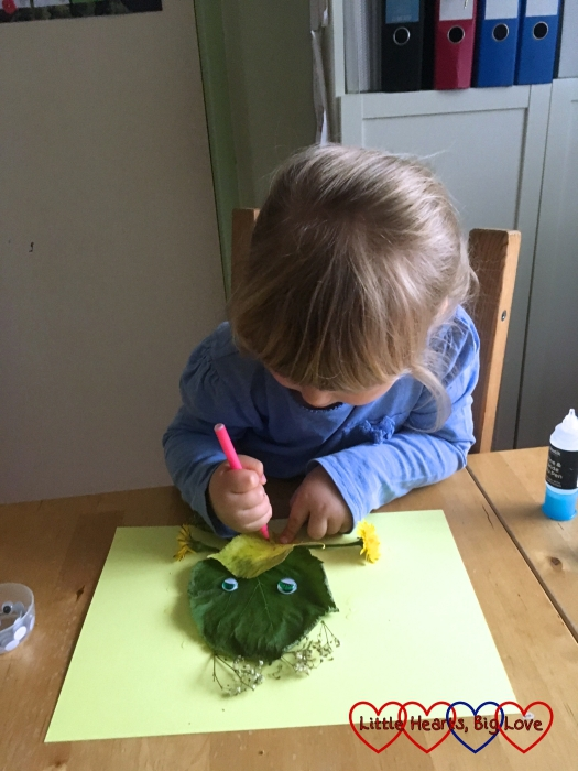 Sophie adding a little detail to her leaf monster picture with a felt tip pen