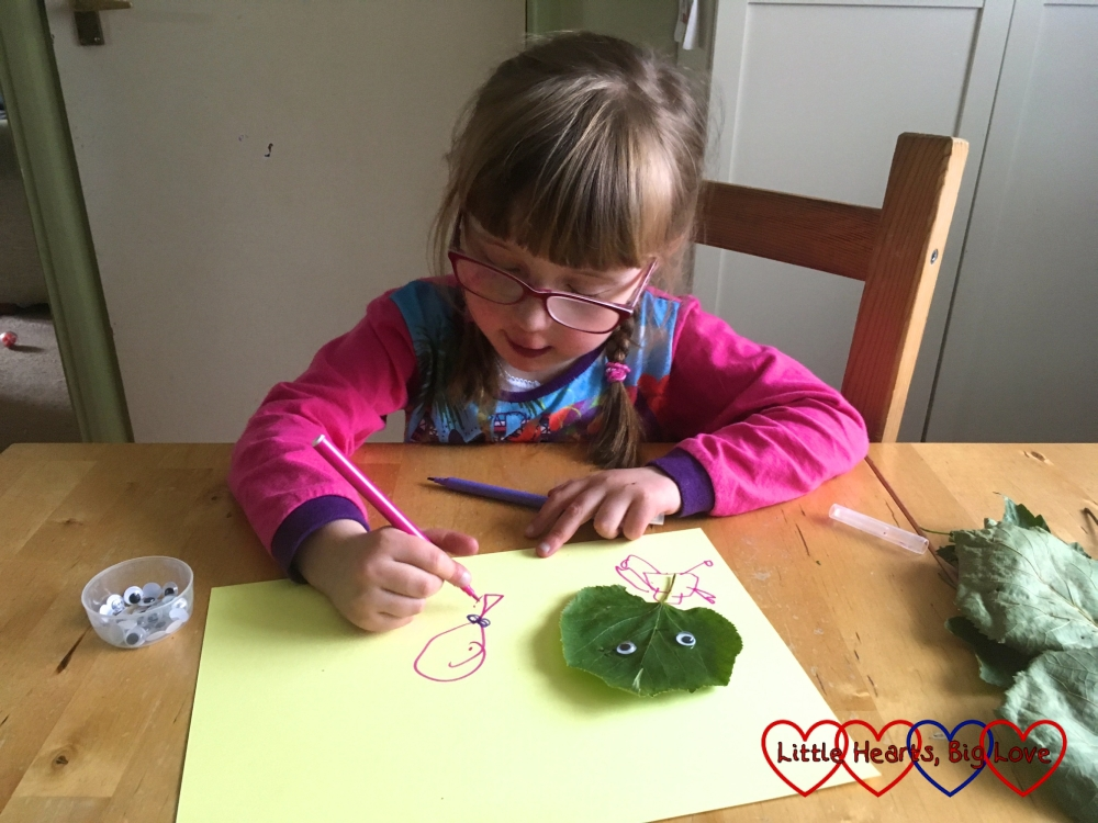 Jessica drawing some detail on to her leaf monster picture
